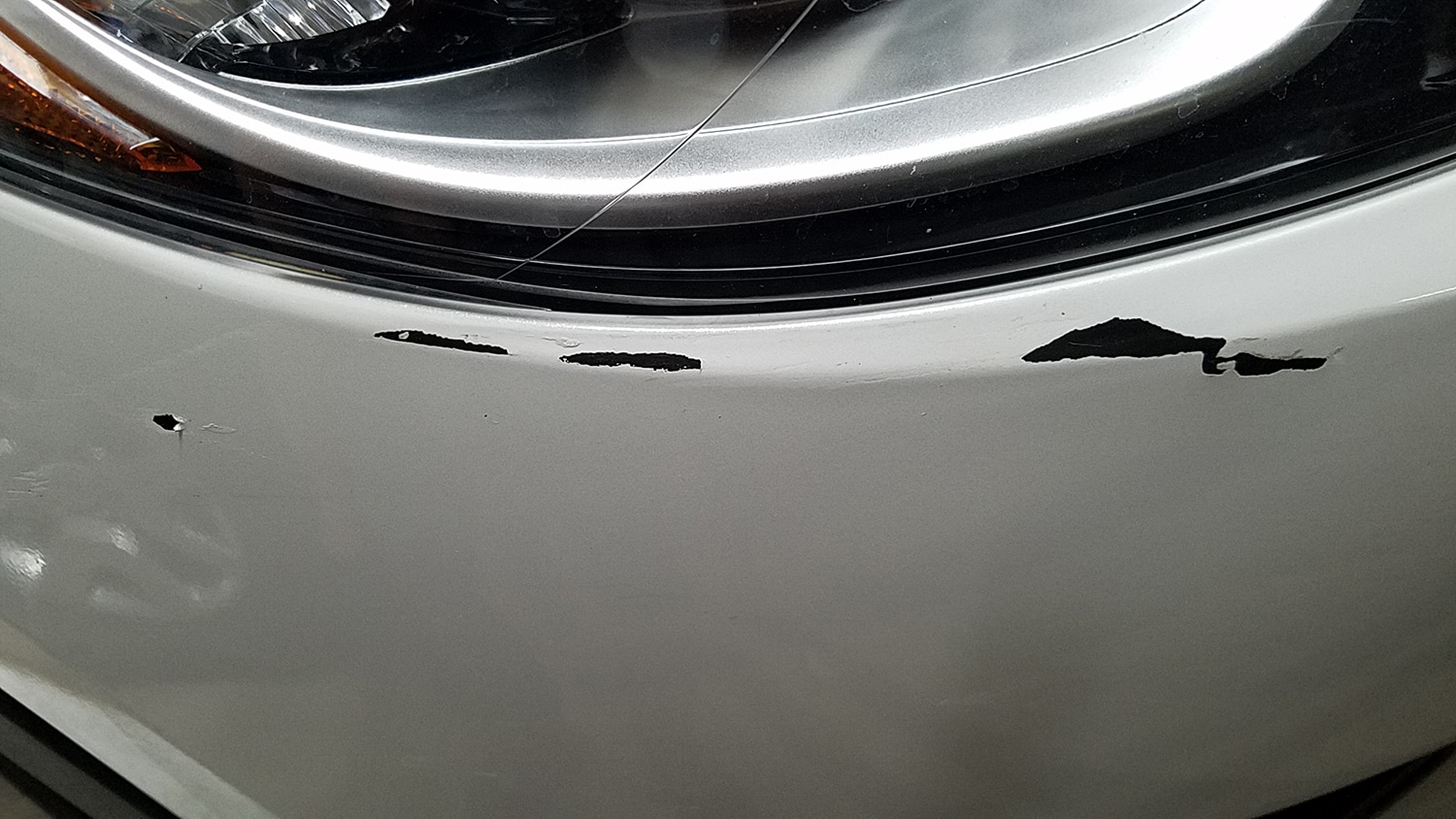 There's a closeup of a car with chipped paint by the headlight. There's a tire reflected on the car.