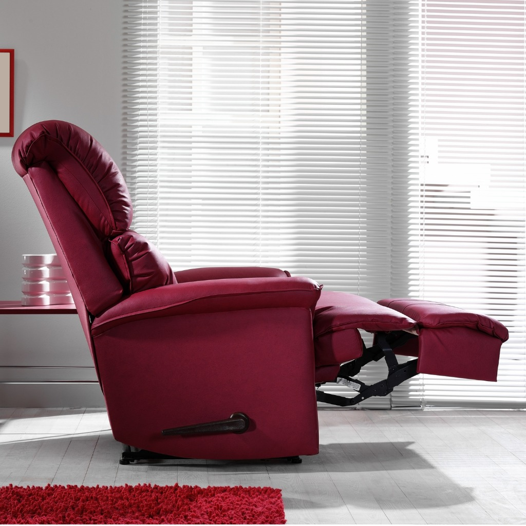 Recliner chair in the center of the image. Around it is open blinds, creating a brighter effect.