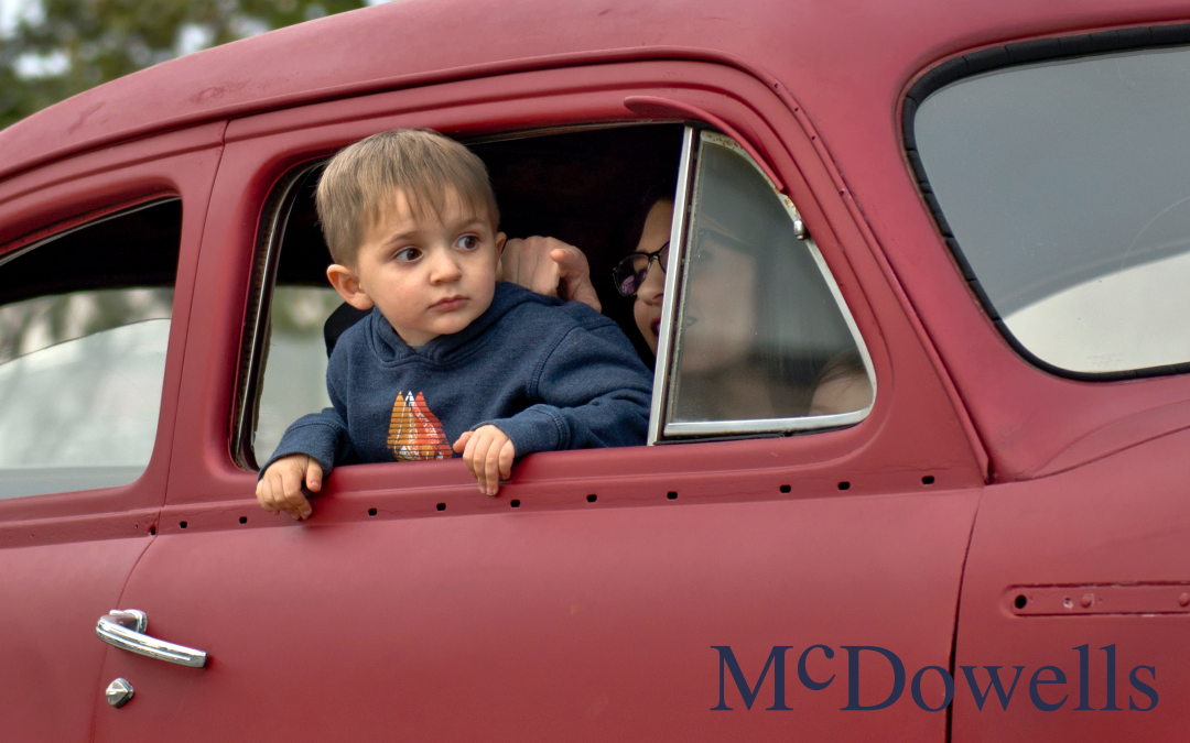 A toddler peeking outside of a car window. The car is a vintage red colored sedan.