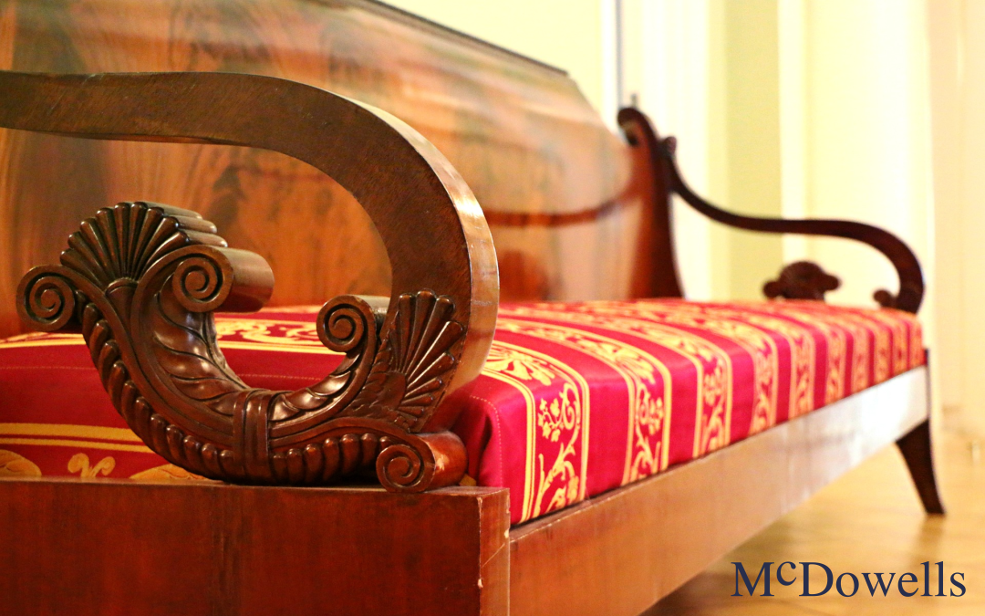 an antique wood bench with a red and gold striped cushion pattern
