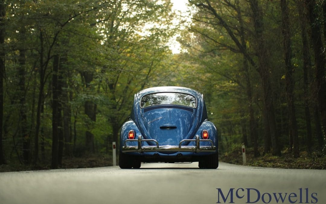 Restored vintage blue VW Beetle drives down a road through the forest.