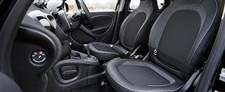 The interior of a car with the front two leather seats, the dashboard, and the steering wheel.
